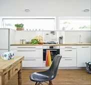 White kitchen with long ribbon windows and dining area