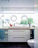 Modern bathroom with glass wall and tilting bullseye windows