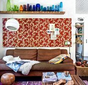 Vases arranged by colour and patterned panel on wall above leather sofa