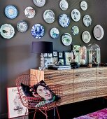 Decorative wall plates on grey wall above sideboard and metal chair