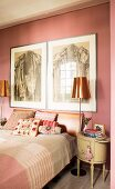 Bedroom in shades of pink with two huge artworks above wall