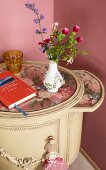Small vase of flowers on Baroque bedside table with floral top