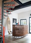 Bar, surfboard, steel girders and spiral staircase in industrial loft apartment