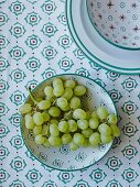 Grapes in a green-and-red patterned bowl on a matching tablecloth