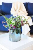 Glass vase of wild flowers on white side table in front of dark blue couch