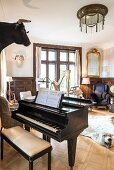 Grand piano and bench in traditional music room with Art-Nouveau ceiling light above polar-bear rug on oak parquet floor