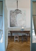 Rustic wooden table and two stools below painting seen through open door