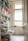 Bookcase and old window in toilet in renovated period apartment