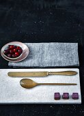 Chocolates and cutlery on marble board and small bowl of cranberries on cloth