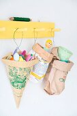 Paper bags reused to store plastic spoons and other utensils hung from yellow coat rack by florists' wire
