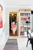 Girl on swing in doorway next to white shelving
