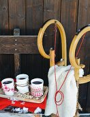 White china beakers of mulled wine with fabric holders and wooden sledge outside rustic hut