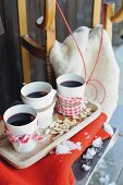 White beakers of mulled wine wrapped in fabric on wooden tray with wooden sledge in background