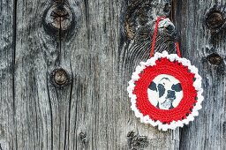 Picture of cow with round, crocheted frame on weathered board wall
