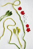 Rote und weisse Häkelblüten mit grünem Häkelschnur