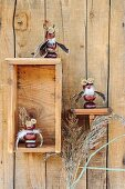 Figurines made from horse chestnuts on rustic wall bracket and in wooden box mounted on board wall