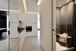 Open-plan hall area in designer apartment with white, fitted kitchen counter, sliding door and view into bathroom