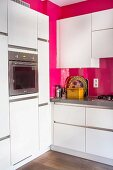 White, modern kitchen with hot pink walls