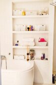 Masonry shelving with white mosaic tiles above bathtub