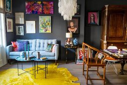 Eclectic furnishings and pictures on grey wall in living room