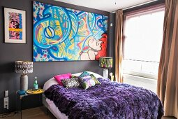 Colourful graffito-style artwork above bed with purple fur blanket