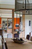 Blick vom Esstisch mit verschieden farbigen Stühlen ins Wohnzimmer