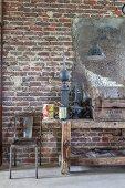 Alte Werkbank und Metallstuhl vor einer Backsteinwand mit blindem Spiegel