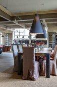 Stühle mit Hussen um einen Esstisch im Fabrikloft