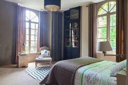 Elegantes Schlafzimmer mit Bogenfenstern und Barocksessel