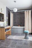 Badezimmer mit grauen Fliesen, Wanne mit Himmel-Vorhängen