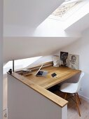 Custom study area with wooden desk below skylight