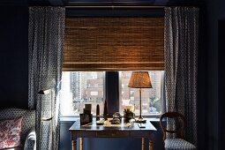 Antiker Schreibtisch mit Tischlampe vor Fenster mit Bambusrollo und blau-weiß gemusterten Vorhängen, Sessel und Stuhlpolster mit gleichem Stoffmuster
