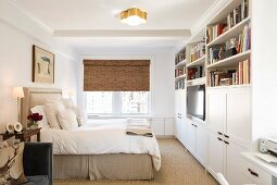 White fitted cupboards and double bed with upholstered headboard in bedroom