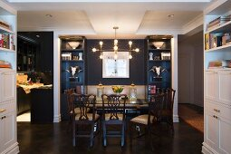 Symmetrical ornaments in dark blue fitted shelves in open-plan eclectic dining area