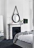 Graues Hussenbett und schwarzer Kamin mit Marmorverkleidung im Schlafzimmer