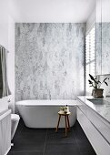 Designer bathroom with free-standing bathtub in front of marble tiles and black floor tiles