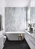 Designerbad mit freistehender Badewanne vor Marmorfliesen und schwarzen Bodenfliesen