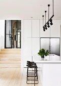 weiße Kücheninsel und Barhocker unter Lichtschiene mit schwarzen Strahlern in offener Küche