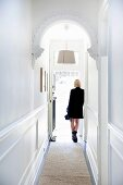 Hallway with white wood paneling and stucco arch, woman dressed in black in the background