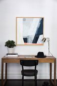 Minimalist precious wood desk and black bistro chair in front of a modern picture