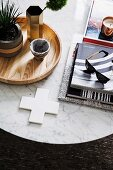 Pile of books with sunglasses and wooden tray with green plant on round marble table