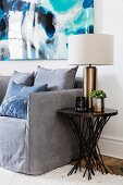 Elegant table lamp on side table next to gray couch, modern picture on wall