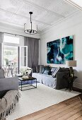 Gray couch set against a modern picture in the living room with stucco ceiling