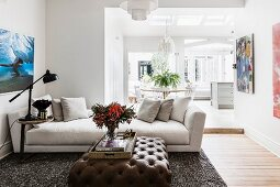 Upholstered table with brown leather upholstery and light couch in an open living room