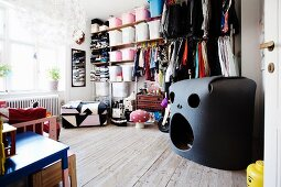 Black foam play den in front of open-fronted shelving system in child's bedroom