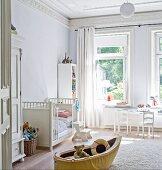 Kinderzimmer in renovierter Stadtvilla mit Spielzeugboot vor weissem Gitterbett
