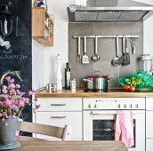 Aufgehängtes Kochbesteck unter Dunstabzug an grau gefliestem Spritzschutz in Küche mit Landhausflair