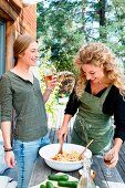 Cheerful young women with pasta salad and wine in garden