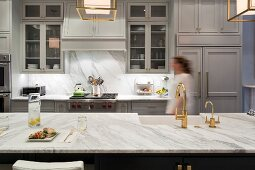 Woman walking through luxurious kitchen with marble worksurfaces
