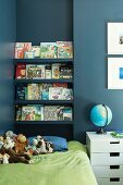Bookcase above bed in child's bedroom with blue wall